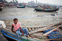 A Myanmar Rohingya fisherman rests on his boat at the slum near the sea in the town of Sittwe early May 23, 2012. REUTERS/Damir Sagolj (MYANMAR)