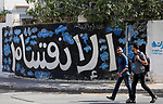 """Palestinians walk past a graffiti reading in Arabic ''Division'' in Gaza City, on September 17, 2017, after Hamas announced it had agreed to steps toward resolving a decade-long split with the Fatah movement and was ready to hold elections. Hamas said it had agreed to key demands made by Fatah: dissolving the so-called """"administrative committee"""", while saying it was ready for elections and negotiations toward a unity government. Photo by Mohammed Asad"""