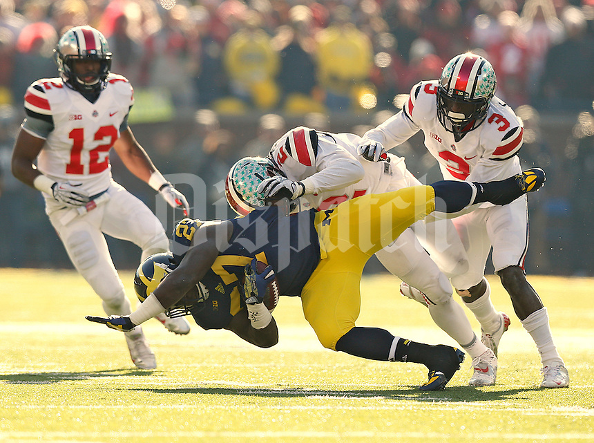 Ohio State Buckeyes line backer Ryan Shazier (2) and Ohio State Buckeyes defensive back Corey Brown (3) team up to take down Michigan Wolverines running back Derrick Green (27) in the second quarter at Michigan Stadium in Ann Arbor, MI on November 30, 2013.  (Chris Russell/Dispatch Photo)
