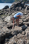 Woman searching among the rocks for treasures, Orcas Island, San Juan Islands, Washington