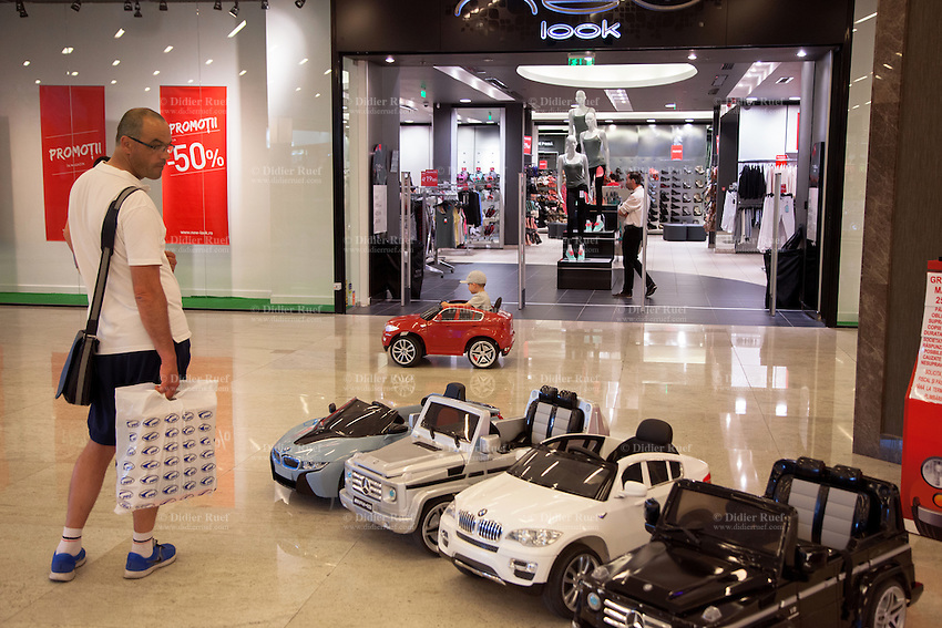 Romania. Iași County. Iasi. Town center. Palas Mall. A young boy drives an electric battery BMW X6 SUV / Remote Control operated ride on car while his father looks at him and waits for him. Other cars for rent, such as the stunning fully licensed Mercedes AMG G55 Luxury Kids 12v Jeep or the luxury sports BMW i8 Concept Electric Ride-On Car. The small private business offer customers the opportunity to rents cars detailed and to scale replica of the road. Parents can pay for their children a five to ten minutes ride in the Palas Mall. Iași (also referred to as Iasi, Jassy or Iassy) is the largest city in eastern Romania and the seat of Iași County. Located in the Moldavia region, Iași has traditionally been one of the leading centres of Romanian social life. The city was the capital of the Principality of Moldavia from 1564 to 1859, then of the United Principalities from 1859 to 1862, and the capital of Romania from 1916 to 1918. 6.06.15 © 2015 Didier Ruef