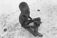 Sudan. Southern part. Bahr El Ghazal. Panthou. Dinka tribe area. A lean and naked boy seats on the ground in a feeding center ran by the ngo (non governmental organisation) MSF Holland ( Médecins Sans Frontières. Doctors without Borders). © 1998 Didier Ruef