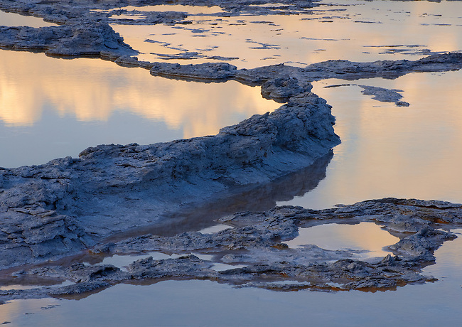 A terrace feature in a geyser pool glows in sunset light along Firehole Lake Drive, Yellowstone National Park