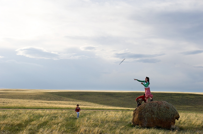 Children of University of Pittsburgh researchers, Emma Capo Stewart, 13, tosses a stick in the direction of brother Owen, 3, as Alex Galik, 9 climbs a rock in the yard of rancher Allen Cook. Cook recently donated a large piece of his Wyoming ranch to the University of Pittsburgh for research. The ranch property features cretaceous rock formations preservibg dinosaur fossils, high-plains grassland ecology and interesting tectonic geology for study by the students and faculty of Pittsburg, the University of Wyoming and the Carnegie Museum. (photo/Kevin Moloney)