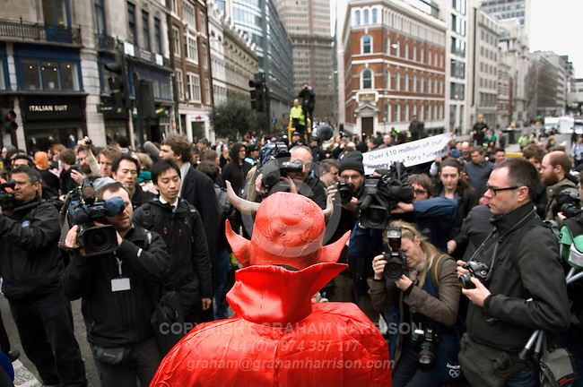 Photographers take pictures of a demonstrator in red cape and devil mask with sign 'Where was her respect for Goldthorpe and the miners?' after the funeral cortege had passed Ludgate Circus during the funeral of Margaret Thatcher, London 17 April 2013.<br /> <br /> Margaret Thatcher (1925-2013) was a radical Conservative politician and British Prime Minister from 1979 to 1992.  <br /> <br /> PHOTO COPYRIGHT GRAHAM HARRISON graham@grahamharrison.com<br /> +44 (0) 7974 357 117<br /> Moral rights asserted.