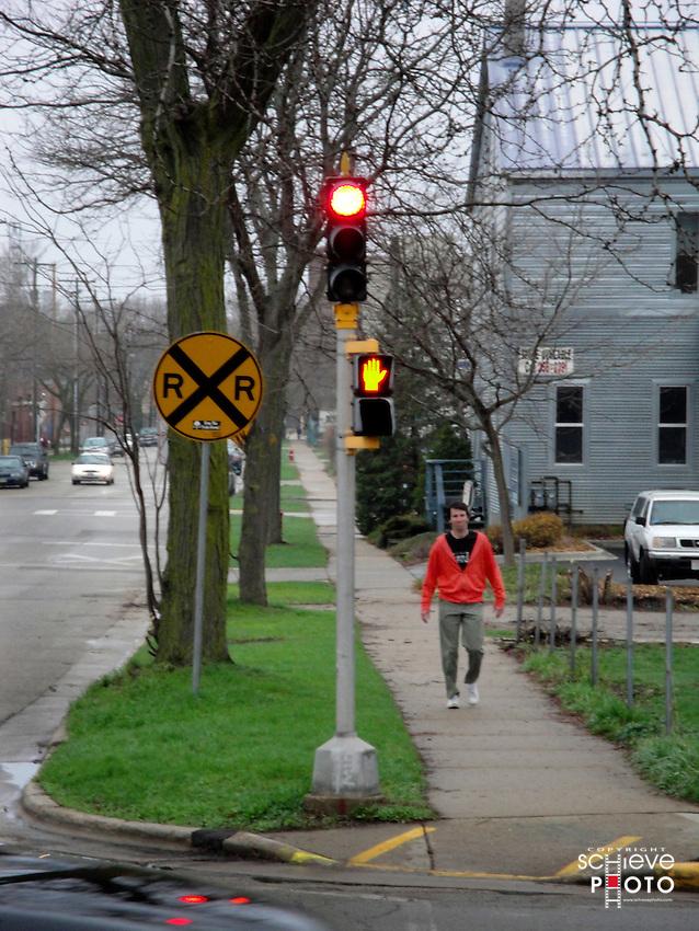 Orange sweatshirt man on sidewalk.