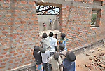 Children anxiously observe construction of their new school in the Southern Sudanese village of Mankaro. The school is being constructed by the United Methodist Committee on Relief (UMCOR). Families here are rebuilding their lives after returning from refuge in Uganda in 2006 following the 2005 Comprehensive Peace Agreement between the north and south. . NOTE: In July 2011, Southern Sudan became the independent country of South Sudan