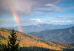Idaho, Eastern,Caribou Targhee National Forest. A brief autumn  rain squall produces a colorful rainbow over the autumn colors in the Caribou Mountains.