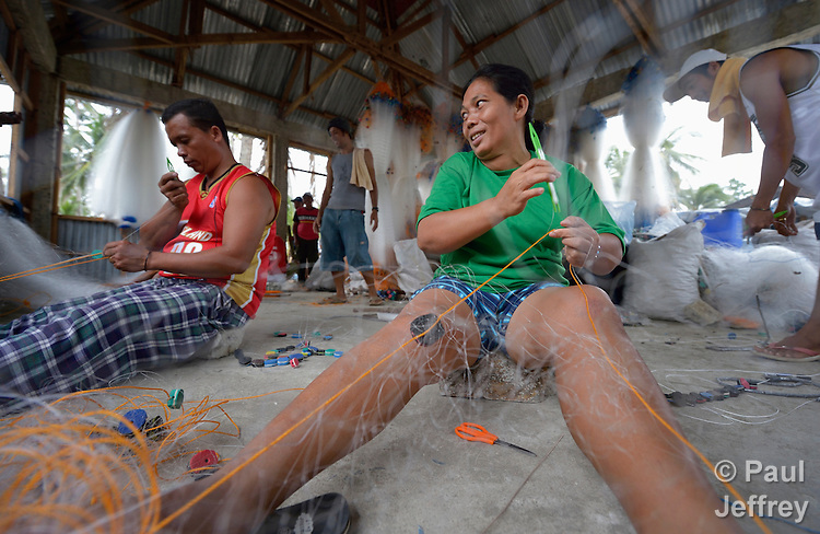 Jeanette Quilitano fabricates new fishing nets on Jinamoc Island, part of the municipality of Basey in the Philippines province of Samar that was hit hard by Typhoon Haiyan in November 2013. The storm was known locally as Yolanda, and left most of the island's boats, nets, and houses destroyed. The community received some new boats from the government, and material for new nets from a media conglomerate. The ACT Alliance has been providing a variety of assistance to survivors, including cash for work and temporary housing, and is planning a long-term rehabilitation program with residents that will include permanent housing, schools, agricultural development, and water and sanitation facilities.