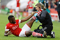 Dimitri Cavare of Barnsley (L) is seen to by a team physiotherapist during the Sky Bet Championship match between Barnsley and Swansea City at Oakwell Stadium, Barnsley, England, UK. Saturday 19 October 2019