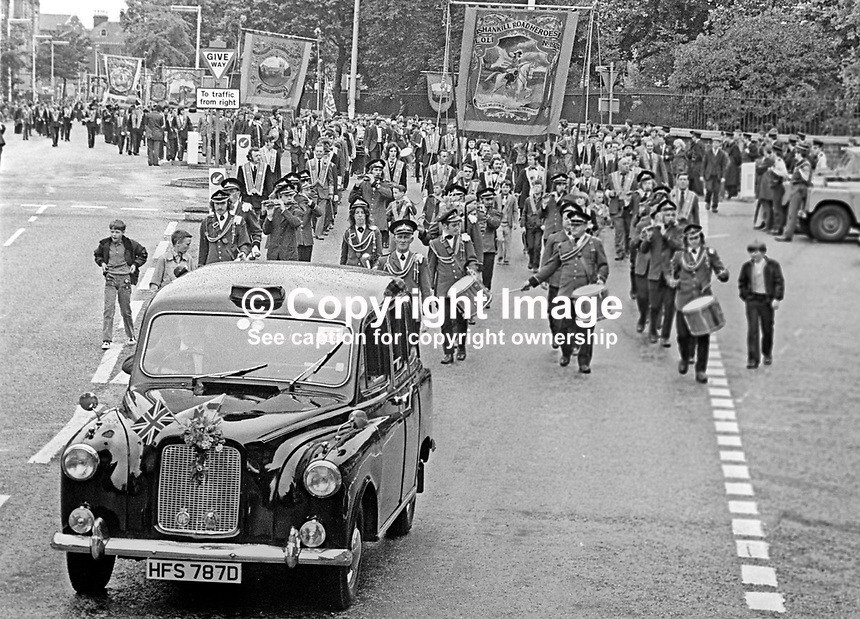 Twelfth, 12th of July, Orangemen's parade, Belfast, N Ireland, UK, 1973 - many lodges rent black taxis and in some cases swish limousines to accompany the marchers so lodge members, especially the elderly and infirm, could get rest &amp; recuperation,197307120503v<br />