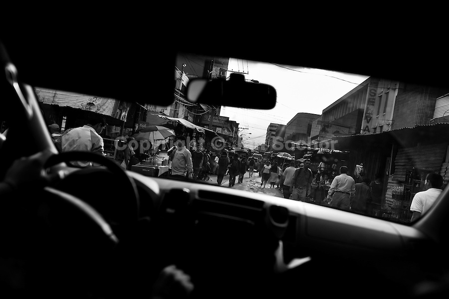 A street in the city center seen from the Police patrol vehicle in San Salvador, El Salvador, 13 May 2011. During the last two decades, Central America has become the deadliest region in the world that is not at war. According to the UN statistics, more people per capita were killed in El Salvador than in Iraq, in recent years. Due to the criminal activities of Mara Salvatrucha (MS-13) and 18th Street Gang (M-18), the two major street gangs in El Salvador, the country has fallen into the spiral of fear, violence and death. Thousands of Mara gang members, both on the streets or in the overcrowded prisons, organize and run extortions, distribution of drugs and kidnappings. Tattooed armed young men, mainly from the poorest neighborhoods, fight unmerciful turf battles with their coevals from the rival gang, balancing between life and death every day. Twenty years after the devastating civil war, a social war has paralyzed the nation of El Salvador.