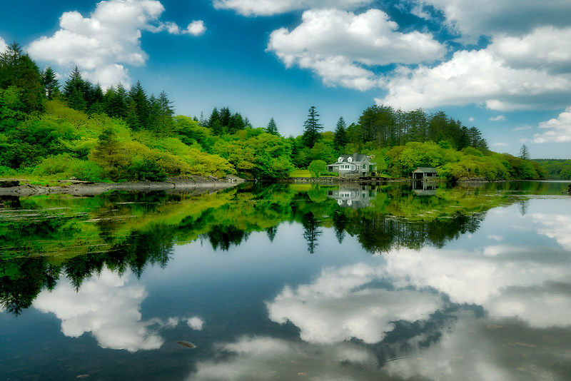 Still waters of Ballynahinch River with house. Connemara. County Galway, Ireland