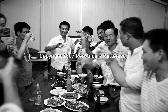 NDOLA, ZAMBIA MARCH 27: Chinese road construction workers have a farewell dinner and drinks for a colleague who is returning to China the next day on March 27, 2007 in Ndola, Zambia. They work for China Henan, a China based company. They are building several roads in Zambia. Chinese companies are often the lowest bidders for contracts, pricing out the more expensive European companies. The Chinese people often live where they work and rarely interact with the local population. Most Chinese don't speak English and they are mostly staying in the compounds cooking their Chinese food, and watching Chinese Television and DVDs. Tens of thousands of Chinese has come to Africa the last years to work in infrastructure projects and businesses. (Photo by Per-Anders Pettersson)..