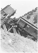 View of RPO #121 and combine #242 hanging from a Barranca Hill trestle following the wreck of train #425.<br /> D&amp;RGW  Barranca Hill, NM  7/17/1929