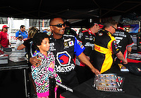 Mar. 10, 2012; Gainesville, FL, USA; NHRA top fuel dragster driver Antron Brown poses for a photo with a fan during qualifying for the Gatornationals at Auto Plus Raceway at Gainesville. Mandatory Credit: Mark J. Rebilas-