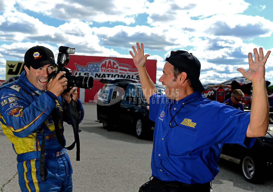 Sept 8, 2012; Clermont, IN, USA: NHRA funny car driver Ron Capps (left) jokingly takes pictures of NHRA photographer Marc Gewertz during qualifying for the US Nationals at Lucas Oil Raceway. Mandatory Credit: Mark J. Rebilas-