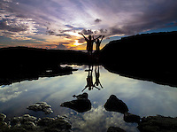 A silhouette of two young girls opening their arms with joy as the sun sets over Keahole Point, Kailua-Kona, Big Island.
