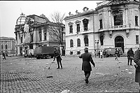 "ROMANIA, Pta. Palatului, today Pta. Revolutiei, Bucharest, 25.12.1989<br /> People rise against Ceausescu. The dictator has fled the city on dec. 22. At the central square intense figting with unidentifiable ""terrorists"" has been going on. Almost all buildings are damaged or partly destroyed. Cleaning-up.<br /> © Andrei Pandele / EST&OST"