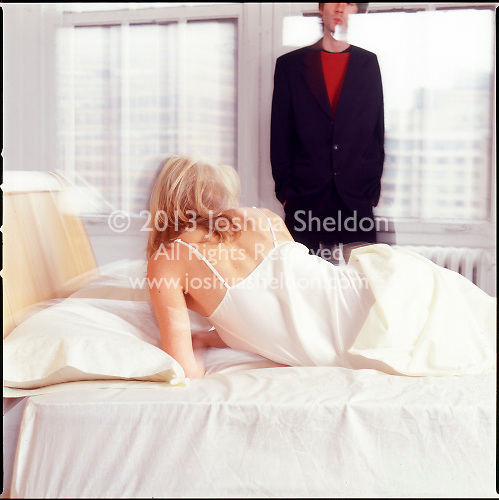 Woman in bed with man in background along windows