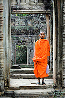 A young Buddhist monk stands framed in an archway of Preah Khan, Angkor, Cambodia. It was built as a royal city in the 12th century AD by Jayavarman VII, one of the Khmer Emperors and served at various times as a monastery and a university. As the latter, it employed over 1,000 teachers and about 98,000 ancillary staff.