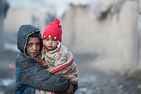 The Chamne Babrak refugee camp in Kabul 5-1-14 A boy with his baby sister.