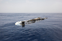 The remnants of a rubber boat are pictured floating in the Mediterranean Sea after having been set ablaze by an unidentified source.
