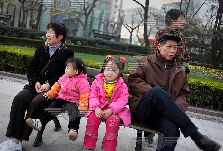 Two young girls, dressed in vivid pink clothes, sit between their grandparents on a park bench.