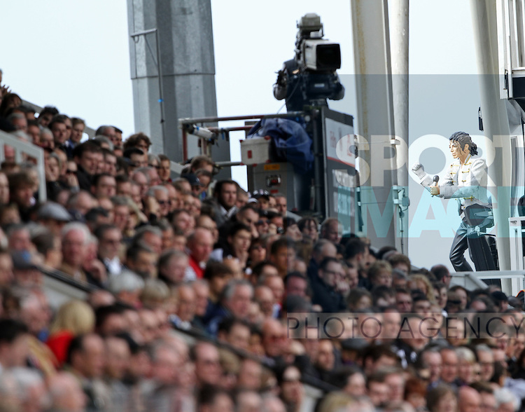 Fulhams fans watch on with the statute of Michael Jackson in the background