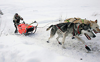 Hugh Neff pushes his sled up the bank of the Yukon river as he arrives in Galena on Saturday afternoon