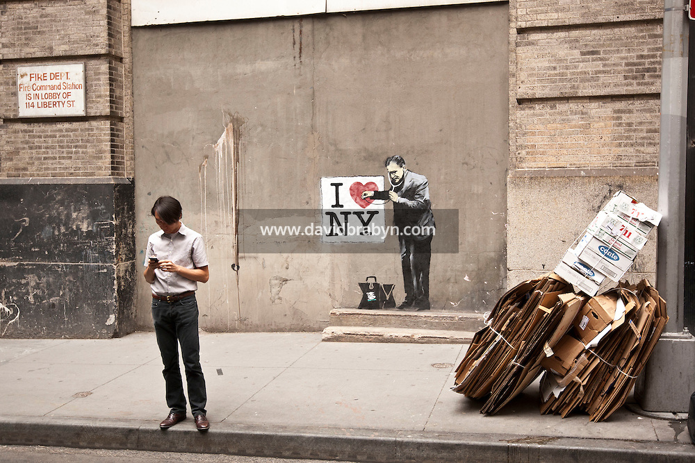 "A man looks at the cellphone picture he just took of the artwork behind him that appears to be by incognito street graffiti artist Banksy on a wall near Ground Zero and Wall Street in New York, USA, 17 May 2010. The British artist is said to be in New York to promote his movie about street art, ""Exit Through the Gift Shop"". Several pieces of artwork have been sighted around the city today."