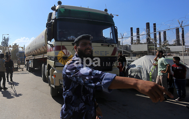 Palestinian policemen keep guard as tankers exit Gaza's power plant in Nuseirat in the center of Gaza strip on June 21, 2017. Egypt began to deliver a million litres of fuel to Gaza, temporarily easing a crisis that has left the Palestinian enclave's two million residents with only a few hours of electricity per day. Photo by Yasser Qudih