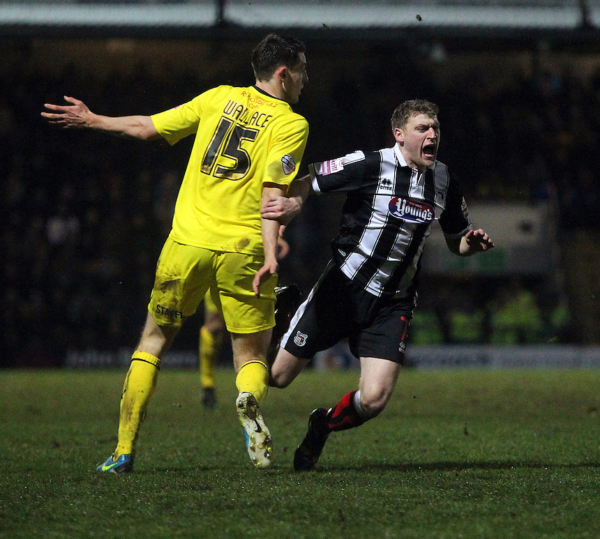 Grimsby Town's Joe Colbeck goes down as he battles with Huddersfield Town's Murray Wallace <br /> <br /> Photo by Rich Linley/CameraSport<br /> <br /> Football - FA Challenge Cup Third Round - Grimsby Town v Huddersfield Town - Saturday 4th January 2014 - Blundell Park - Grimsby<br /> <br />  &copy; CameraSport - 43 Linden Ave. Countesthorpe. Leicester. England. LE8 5PG - Tel: +44 (0) 116 277 4147 - admin@camerasport.com - www.camerasport.com