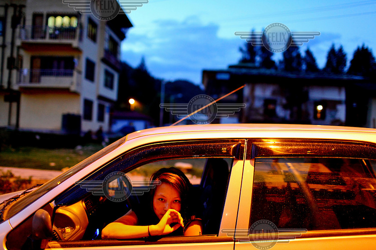 A young girl looking from her car window in Paro.