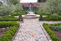 Upscale vegetable garden with cut stone walkway, fence, trellised apple fruit trees and beautiful old barn and fence, circular water pond feature and fountain