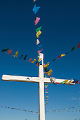 Pontal, Ilheus, Bahia State, Brazil. Cross with colourful plastic bunting blowing in the breeze.