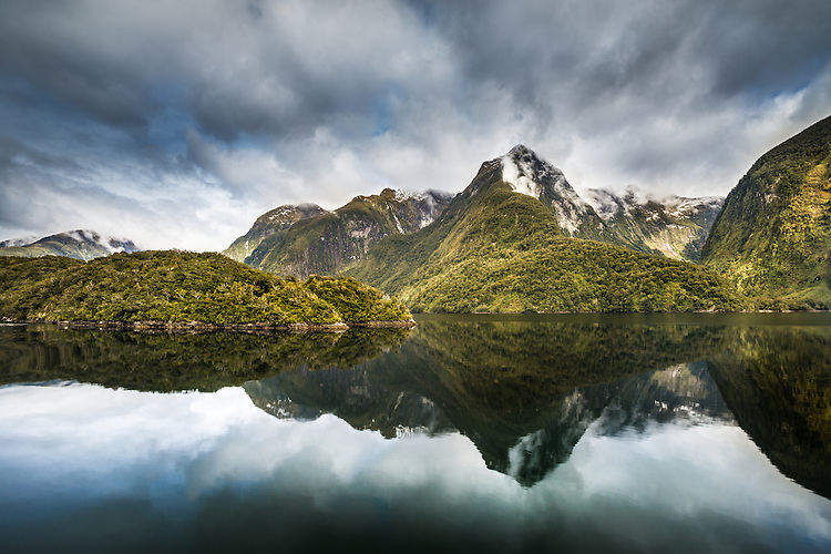 Mirror reflection of mountains and clouds in Doubtful Sound, Fiordland Naitonal Park, South Island, New Zealand - stock photo, canvas, fine art print