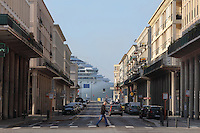 Apartment buildings on the Rue de Paris, designed by Auguste Perret, 1874-1954, who led the reconstruction of Le Havre in the 1950s, after the town was completely destroyed in WWII, and a cruiseship seen at the end of the road, Le Havre, Normandy, France. This is the oldest street in Le Havre and was based on the Rue de Rivoli in Paris, with grand apartment blocks with shops on the ground floor and colonnades along the pavements. The centre of Le Havre is listed as a UNESCO World Heritage Site. Picture by Manuel Cohen