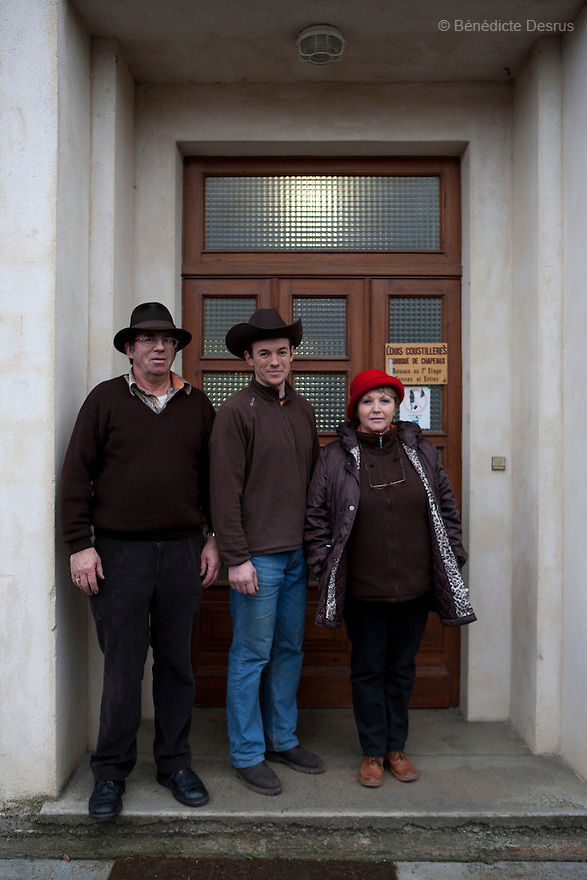 9 december 2009 - Coustilleres' hat factory, Septfonds, France - Jean-Claude Coustilleres, Christophe Coustilleres (son), Michelle Coustilleres (wife) - from left to right - in front of the Coustilleres' hat factory..Septfonds is the heart of French straw hat making, due to its very ancient hatter tradition. The hat making industry had its commercial peak in the late 19th century..Coustillères is a family owned hat making factory that has been making straw hats in Septfonds for nearly 100 years. They make hats from straw, felt, and cloth as well as caps. The current owner is Jean-Claude Coustilleres. He is one of the last hat makers of the region..The straw hat making process is very labor intensive and numerous hands are involved. Nearly all of the equipment is over 100 years old, they use the original presses and tools including aluminium molds and sewing machines and dye their own straw continuing the traditional methods of manufacturing. The hat blocking and shaping, straw braids construction and dyeing are all done by hand..The company works on behalf of fashion houses and makes a variety of regional and historical hats. It produces 2 collections a year distributed by a network of salespeople and through a catalog to clients around the world. Photo credit: Benedicte Desrus