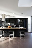 In the kitchen/living area black high-gloss parapan is used in a pleasing contrast to mellow grey stone floors and the Quartz stone of the floating island