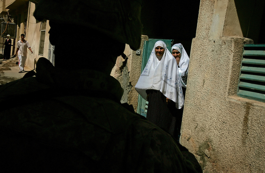 Two elderly Iraqi women peer out from the gate of their apartment building to watch passing American troops as the troops - members of the 4th Battalion 23rd Infantry Regiment 172nd Stryker Brigade - move through the Baghdad Sunni district of Adhamiyah on Friday September 1, 2006. The 172nd was extended at the last moment - with portions of the brigade already back in the States - when they were called upon to bolster security forces in Baghdad seeking to get a handle on a massive wave of sectarian killings in the Iraqi capital.