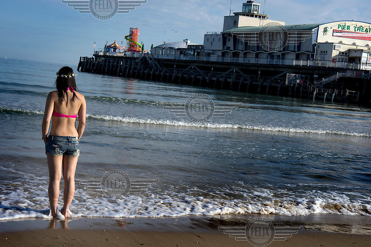 A young woman stands iat the water's edge on the beach in Bournemouth, Dorset. Next to her is the town's pier that dates from the mid-ninetenth century.