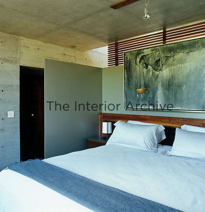 A three-quarter height partition gives the bedroom privacy but allows light to filter through the room