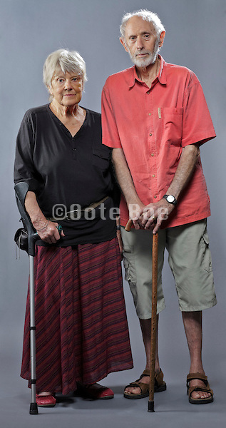 senior couple studio portrait with crutch and walking stick support