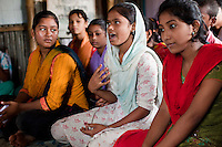 "Rina Akhter Meghla (14, baby blue scarf) speaks of her ordeal during a monthly meeting of a Children's Group in Bhashantek Basti (Slum) in Zon H, Dhaka, Bangladesh on 23rd September 2011. ""I was about to be wed. The groom was already selected. I told my parents that I didn't want to get married now because I just will be a servant to my husband. I wanted to be independent."" Her parents had said that they wanted to marry her off because she was watching too much television and not doing well in school, after which she promised to stop watching TV and improve her grades. Her ambition is to be a police inspector. The Bhashantek Basti Childrens Group is run by children for children with the facilitation of PLAN Bangladesh and other partner NGOs. Slum children from ages 8 to 17 run the group within their own communities to protect vulnerable children from child related issues such as child marriage. Photo by Suzanne Lee for The Guardian"