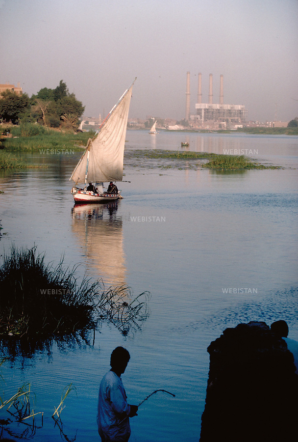 ..Egypt. Cairo. Shubra el-Khema District. 1996. Feluccas on the Nile along the banks where factories stand...Egypte. Le Caire. Quartier de Shubra el-Khema. 1996. Felouques sur le Nil le long des rives ou s'elevent des usines.
