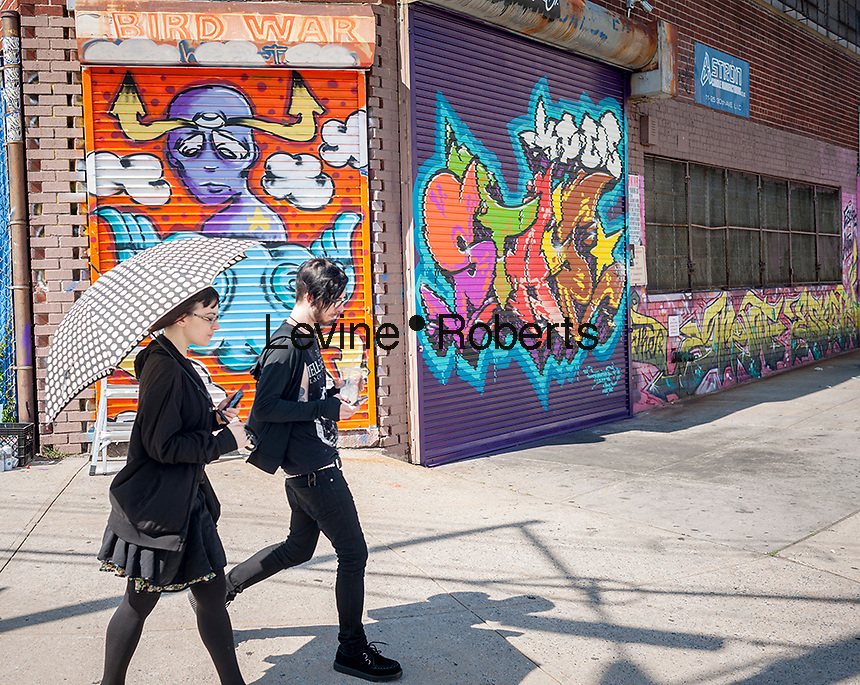 Visitors walk past work at the Welling Court Mural Project in the Astoria neighborhood of Queens in New York on Saturday, June 13, 2015. The annual neighborhood event decorates walls in this industrial part of Astoria. The project is crowd-funded and emerging street artists work side by side with established stars.  (©Richard B. Levine)