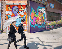 Visitors walk past work at the Welling Court Mural Project in the Astoria neighborhood of Queens in New York on Saturday, June 13, 2015. The annual neighborhood event decorates walls in this industrial part of Astoria. The project is crowd-funded and emerging street artists work side by side with established stars.  (© Richard B. Levine)