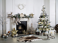 Interior in location house, London. A Christmas decorated scene of a fireplace and Christmas tree.  Stockings hang from the mantelpiece and a reindeer rug lies on the floor.