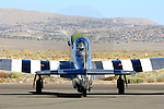"Race #12, ""The Rebel,"" a stock P-51D Mustang flown by Doug Matthews of Wellington, Florida turns the prop while on the tarmac prior to a race at the 2008 Reno National Championship Air Races at Stead Field, Nevada. Matthews, a rookie in 2008, flew the Rolls Royce Merlin powered fighter to a second place finish in the Bronze class with a speed of 350.290 MPH on the 50.12 mile course."